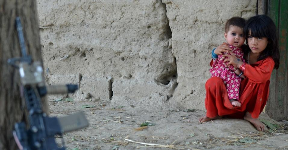 10.jun.2012 - Crianças observam arma de tropas norte-americanas na cidade de Sangin, no Afeganistão