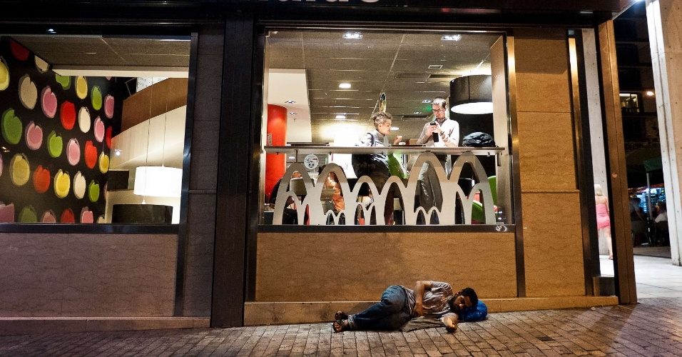 10.jun.2012 - Homem sem teto dorme em frente ao restaurante Mc Donalds no centro de Atenas, na Gr&#233;cia