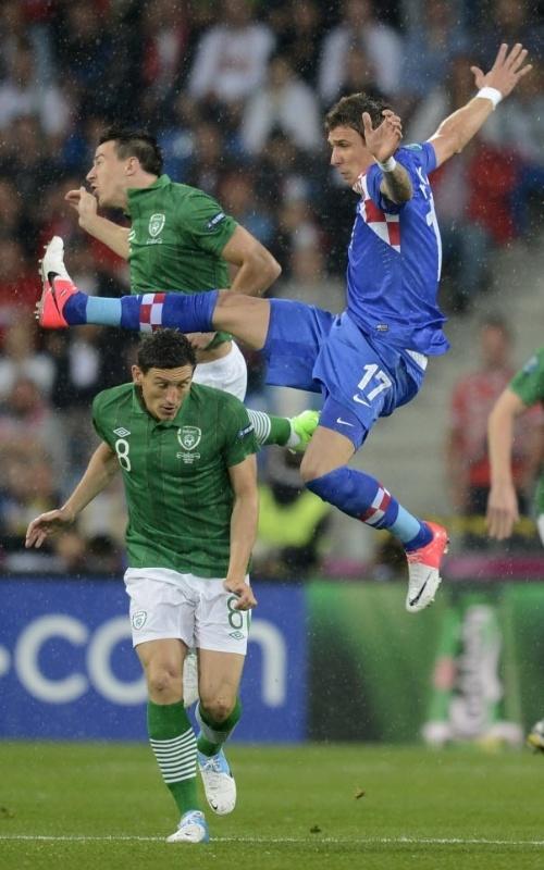 Irlandês Keith Andrews (e.) disputa bola com croata Mario Mandzukic em jogo da Eurocopa em Poznan