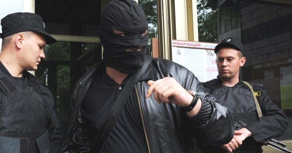 11.jun.2012 - Agente de segurança russo mascarado vasculha casa de blogueiro opositor ao presidente Vladimir Putin