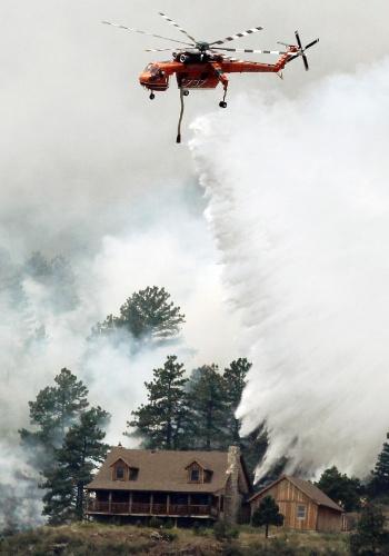11.jun.2012 - Helicóptero tenta conter incêndio que ameaça casa em parque no Estado do Colorado, nos Estados Unidos. O fogo já consumiu cerca de 150 mil km², segundo as autoridades locais