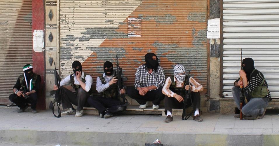 11.jun.2012 - Membros do Exército Livre Sírio descansam em calçada de Damasco, na Síria, com os rostos cobertos e armas na mão