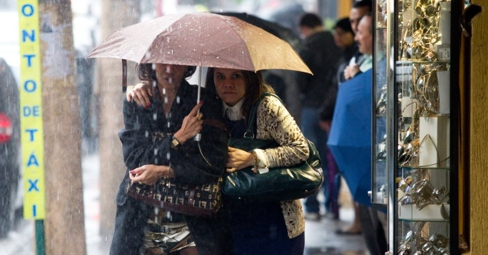 11.jun.2012 - Mulheres se protegem sob o mesmo guarda-chuva durante tempestade que atingiu S&#227;o Paulo nesta segunda-feira (11)