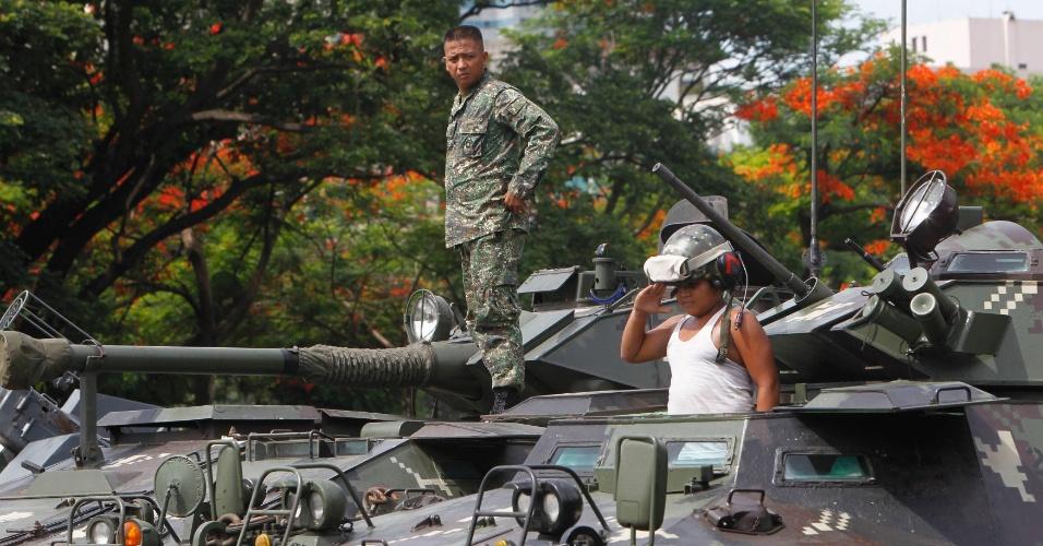11.jun.2012 - Soldado observa menino em cima de tanque blindado, exibido nas preparações para a cerimônia do 114º Dia da Independência das Filipinas em parque de Manila