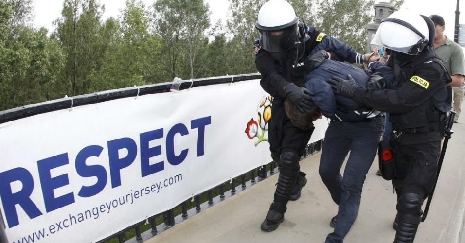 Polícia polonesa detém torcedor em Varsóvia, antes da partida entre Rússia e Polônia. Jogo conta com esquema especial de segurança