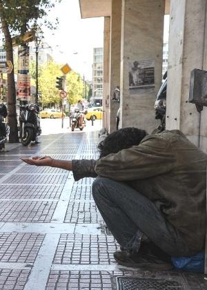 Morador de rua pede esmola em rua de Atenas, capital da Grécia