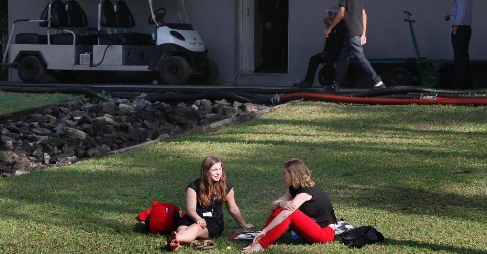 13.jun.2012 - Mulheres descansam no verde entre os pavilhões do Riocentro onde acontece a Rio +20