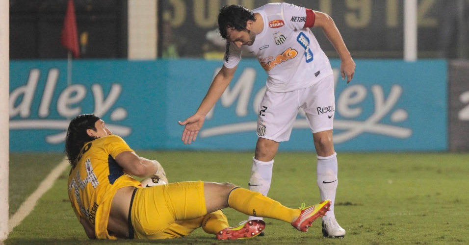 Zagueiro Edu Dracena, do Santos, oferece ajuda para goleiro Cássio, do Corinthians, se levantar