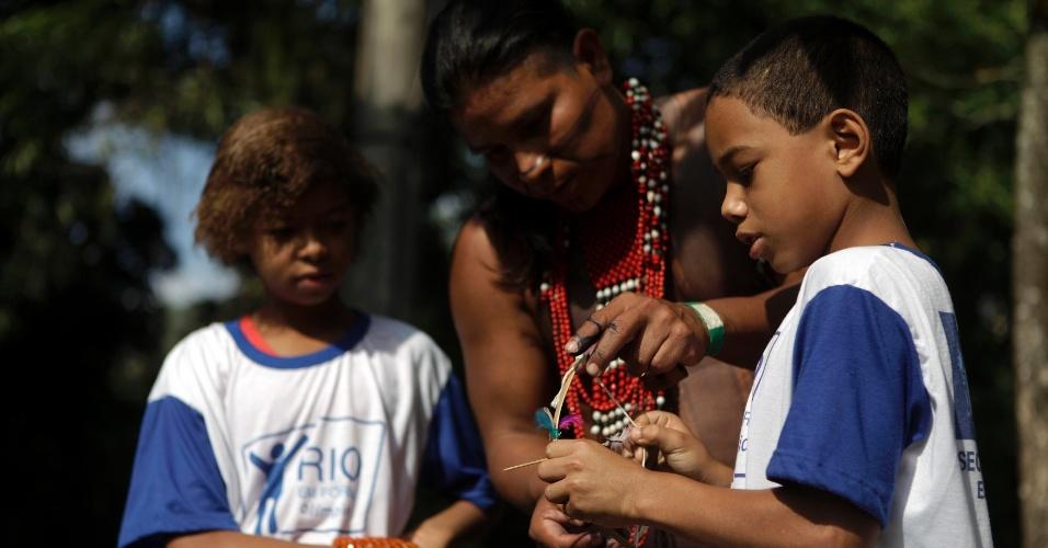 15.jun.2012 - Índio da etnia Caiapó mostra um arco e flecha em miniaturas para estudantes na Aldeia Kari-Oca, durante a Rio+20