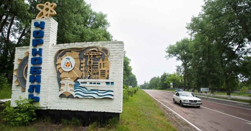 Carro passa pela entrada de Pripyat, na Ucrânia, cidade em que a usina de Chernobyl sofreu acidente