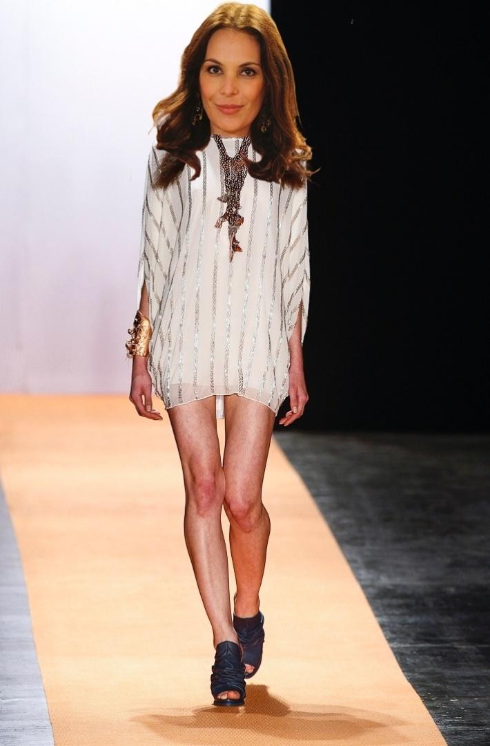 """O figurino de Alexia, interpretada por Carolina Ferraz, é sedutor e ligado nas tendências de moda. A personagem usa muito brilho, texturas e vestidinhos curtinhos e chiques. O look branco com bordado de canutilhos e sapatos pesados de Juliana Jabour combina com o estilo da personagem, por ser """"fashion"""" e elegante, mas revelando as pernas"""