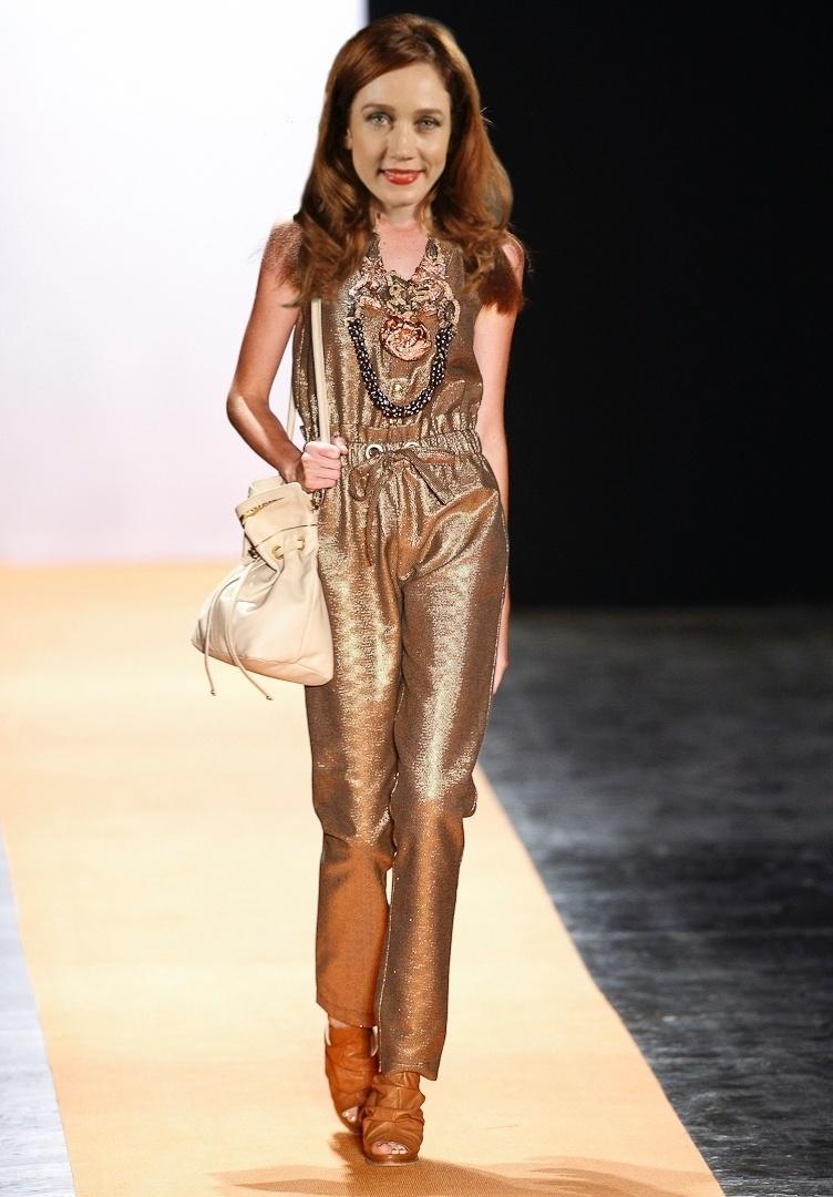 O macacão dourado Juliana Jabour, usado com colares e bolsa de lado é a cara de Noêmia (Camila Morgado)