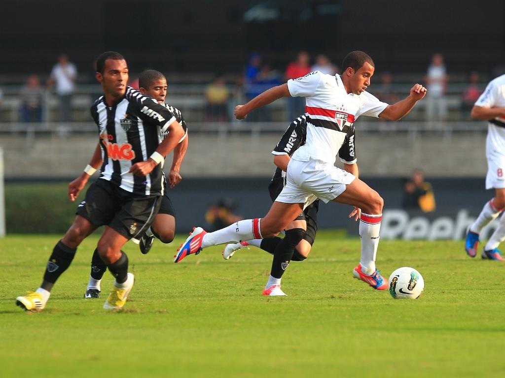 Lucas, meia do São Paulo, passa pela marcação de Richarlyson, do Atlético-MG, durante jogo no Morumbi