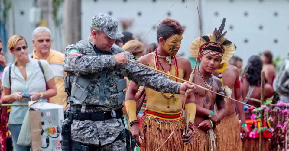Policial da Força Nacional experimenta como usar um arco e flecha, neste domingo (17), na aldeia Kari-Oca, onde estão acampados indígenas da colônia Juliano Moreira, no Rio de Janeiro