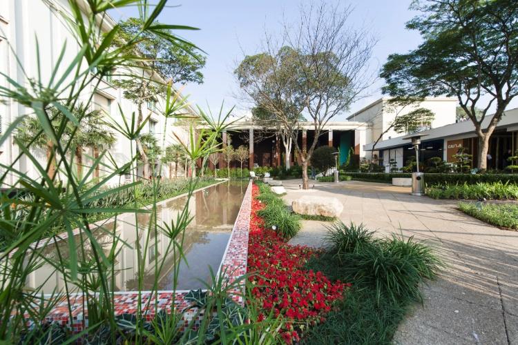 """Os arquitetos Miriam Escobar e Robson de Freitas projetaram a Praça Casa Hotel, uma composição que alia formas orgânicas e geométricas.  Os dois """"tapetes"""" de pisos drenantes convergem para o centro da praça e da fachada do edifício da Casa Hotel. Destaque para o espelho d´água revestido com pastilhas de vidro em tons de vermelho"""