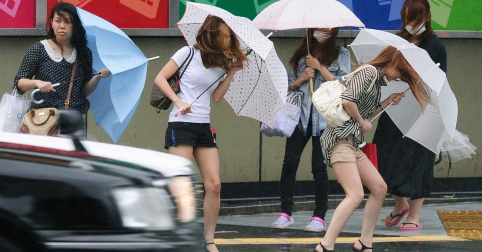 19.jun.2012 - Mulheres sofrem com a chuva e o vento forte causados pelo tuf&#227;o Guchol em Nag&#243;ia, no Jap&#227;o