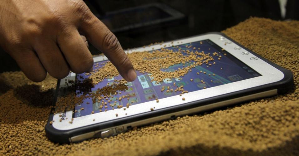 19.jun.2012 - O tablet Toughpad, da Panasonic, é exibido coberto de areia durante a CommunicAsia, feira de eletrônicos que ocorre em Cingapura. O portátil, que pesa 950 gramas, é voltado para o ambiente corporativo e, em função disso, aguenta bem eventuais acidentes como queda, derramamento de água e poeira. Ele será vendido a partir de setembro na Ásia por US$1.599