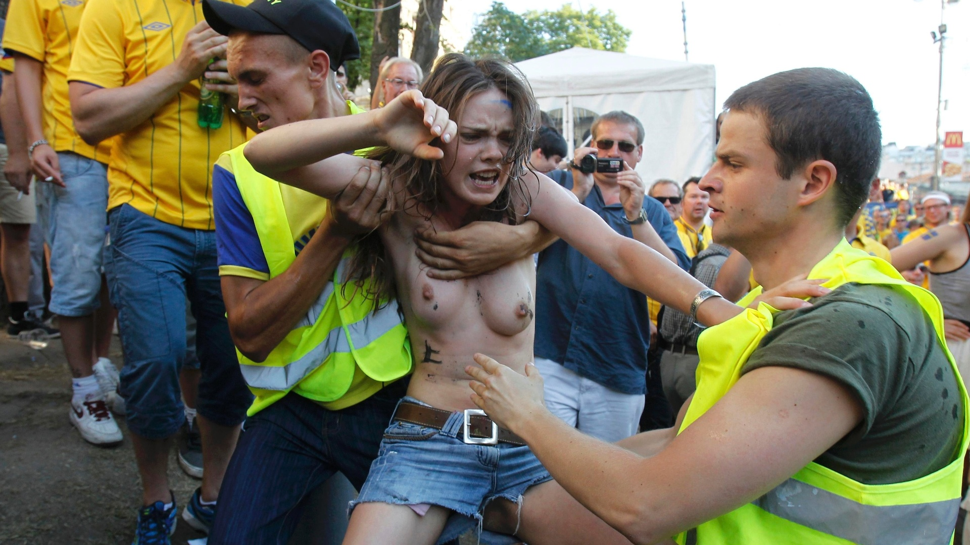 Ativista do Femen  contida por agente de segurana aps protestar contra a realizao da Euro