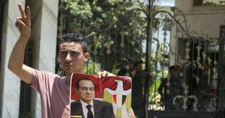 20.jun.2012 - Apoiador do ditador deposto Hosni Mubarak v&#227;o &#224; porta do hospital onde est&#225; internado o ex-presidente eg&#237;pcio, na capital do pa&#237;s, Cairo