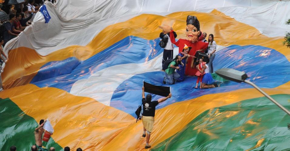 20.jun.2012 - Ativistas levam bandeira gigante do Brasil e boneco que representa Dilma Rousseff para protestar na Rio+20
