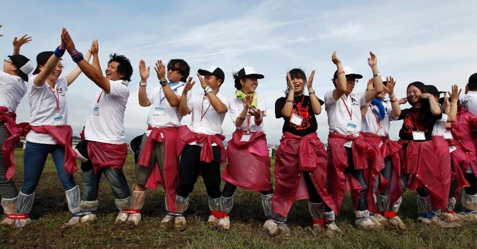20.jun.2012 - Grupo formado por 450 turistas japoneses e 152 chineses celebra após bater o recorde mundial do maior número de pessoas em uma corrida de pernas juntas, em parque de Taiwan, na China