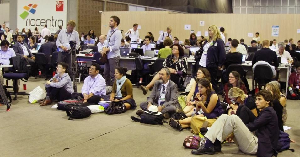 20.jun.2012 - Jornalistas disputam espaço e até sentam no chão para assistir aos líderes de Estado discursando na Rio+20