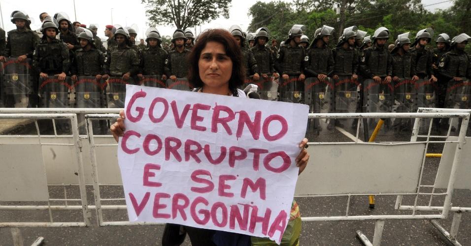 20.jun.2012 - Manifestante segura cartaz com crítica ao governo em frente ao Riocentro, local em que é realizada a Rio+20, Conferência da ONU sobre Desenvolvimento Sustentável