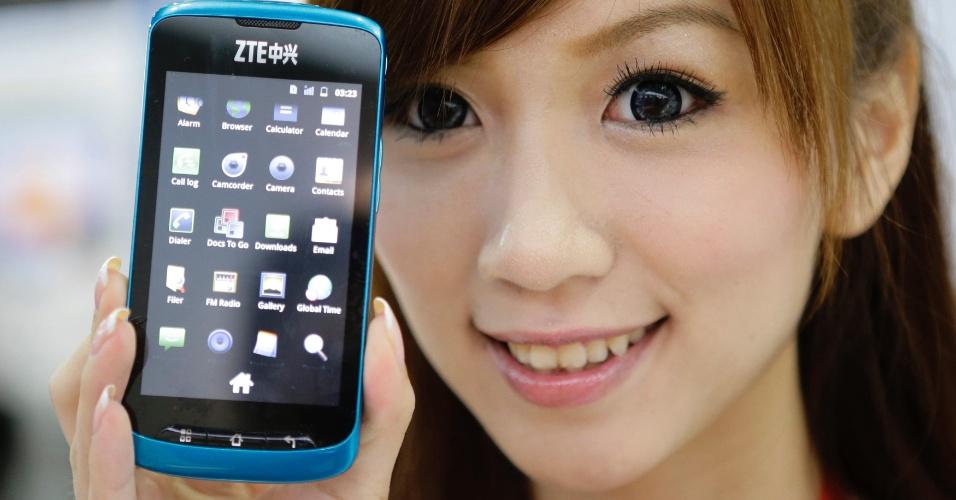 21.jun.2012 - Smartphone ZTE V882 é mostrado por modelo durante a CommunicAsia, feira de eletrônicos em Cingapura. O aparelho é à prova d'água, poeira e choques, além de vir com Android 2.3, tela de 3,8 polegadas LCD e câmera de 5 megapixels