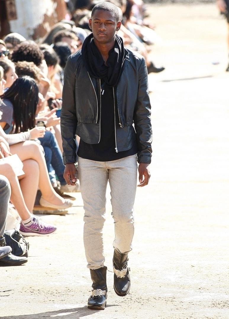 Na coleção da Cavalera, desfilada ao ar livre, o modelo apresenta um look com jaqueta, calça, cachecol e botas de couro