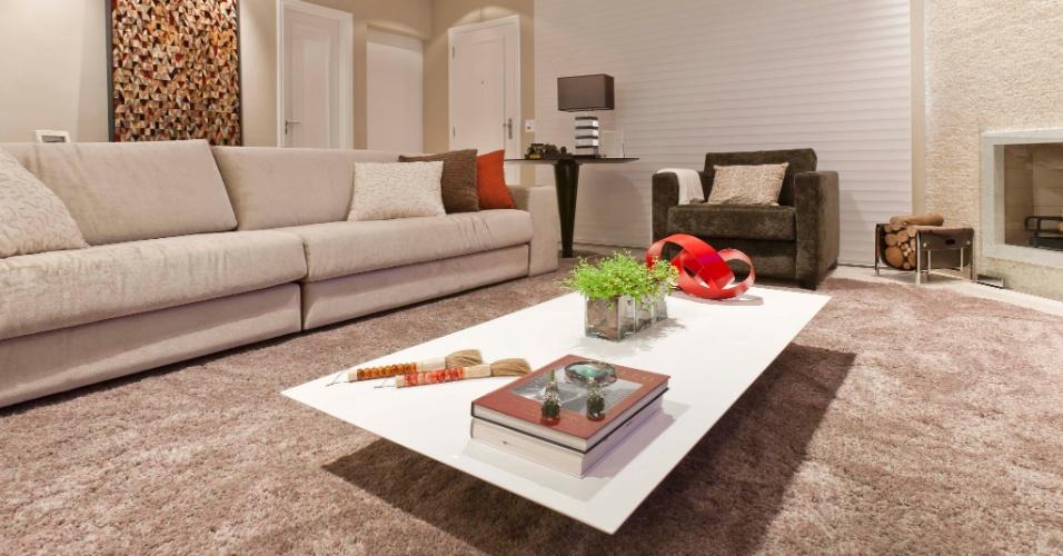 A persiana em tecido é da linha Silhouette, da Luxaflex e motorizada, integra-se ao sistema de automação da casa. Sofás Artefacto, tapete Avanti e mesa de centro laqueada branca Dpot, em forma trapezoidal, parece flutuar na sala de estar. A escultura vermelha, sobre a mesa, é Arte Aplicada; os objetos de decoração, L'oeil.  A casa em São Caetano do Sul (SP) tem reforma assinada pela arquiteta Mayra Lopes