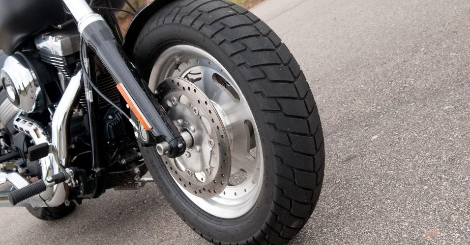 O pneu dianteiro (de medidas 130/90) tem perfil alto, o que compromete a troca rápida de direção, mas prioriza o conforto