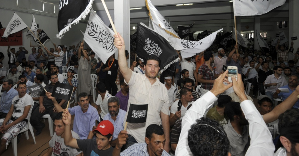 24.jun.2012 - Militantes do partido isl&#226;mico tunisiano Hizb Ettahrir, que n&#227;o &#233; reconhecido pelo governo, gritam slogans e levantam bandeiras durante congresso organizado para pedir a volta do califado na Tun&#237;sia