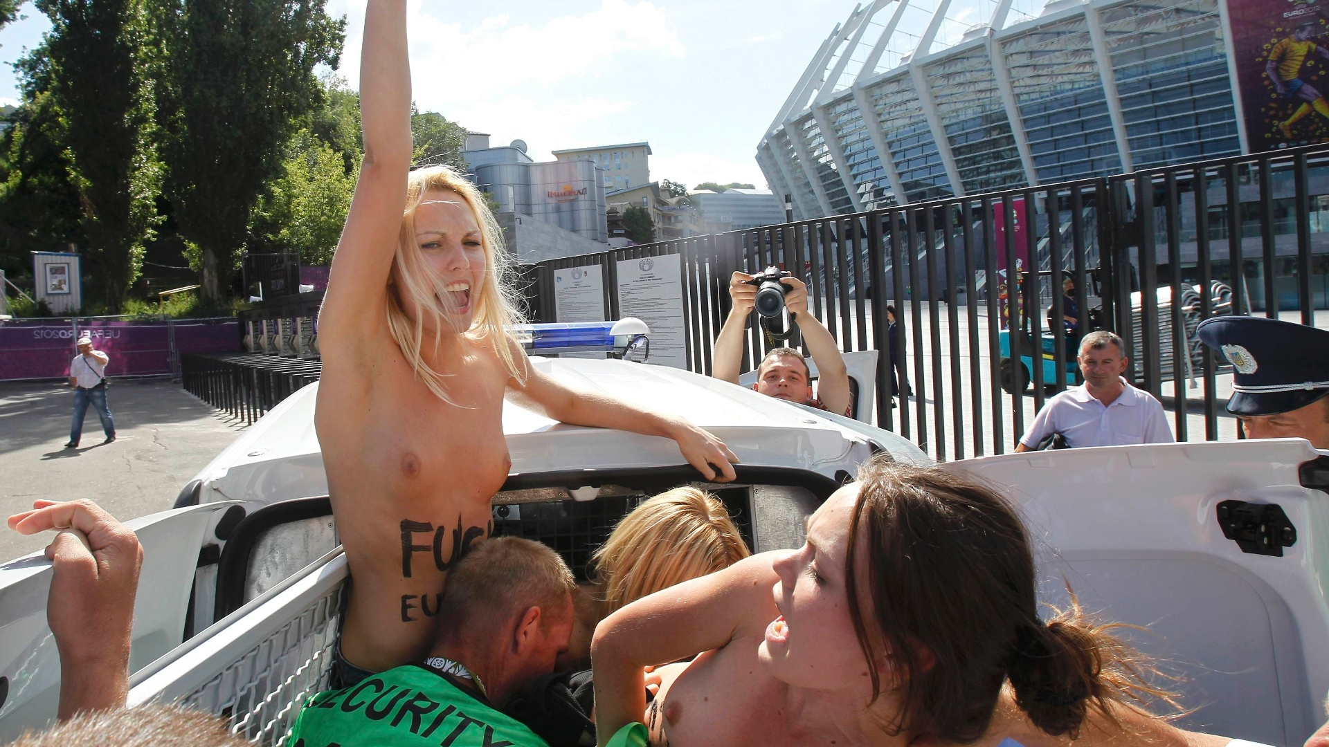 24.jun.2012 - Policiais detm manifestantes do grupo feminista Femen que protestavam no estdio olmpico em Kiev, na Ucrnia, durante partida do campeonato Euro 2012. O grupo tem organizado vrios protestos sob o lema 