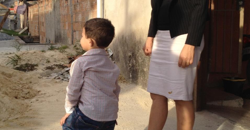 25.jun.2012 - A mãe de Eliza Samudio, Sônia de Fátima Moura, aparece na porta de casa com o neto, cuja partenidade é atribuída ao goleiro Bruno Souza