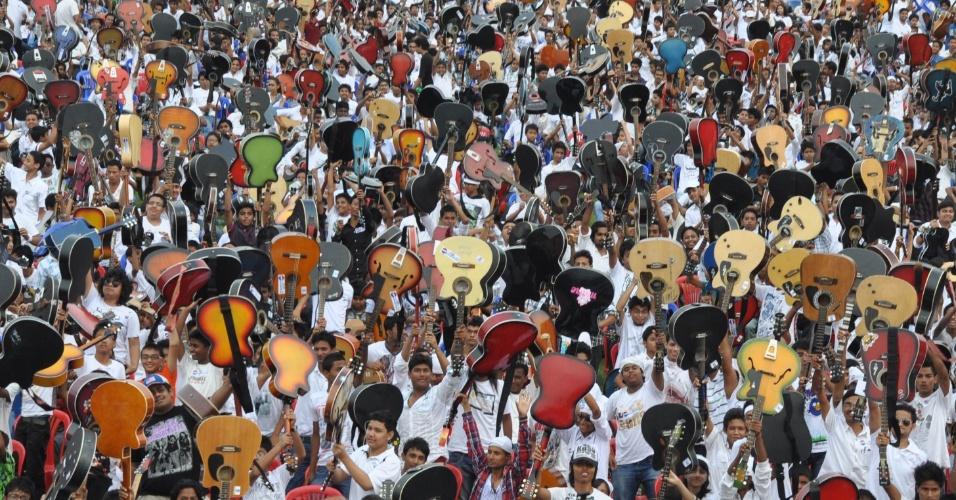 25,jun.2012 - Indianos comemoram após bater recorde do maior número de pessoas tocando violão, em Guwahati, na Índia. De acordo com a organização do concurso, cerca de 5.400 pessoas participaram do evento