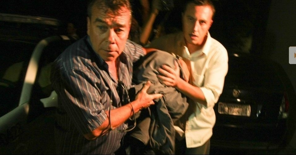 6.jul.2010 - Coberto por um casaco, o adolescente de 17 anos, primo do goleiro Bruno, do Flamengo, deixa a Delegacia de Homicídios, na Barra da Tijuca, zona oeste do Rio de Janeiro, após prestar longo depoimento na noite desta terça-feira (6).