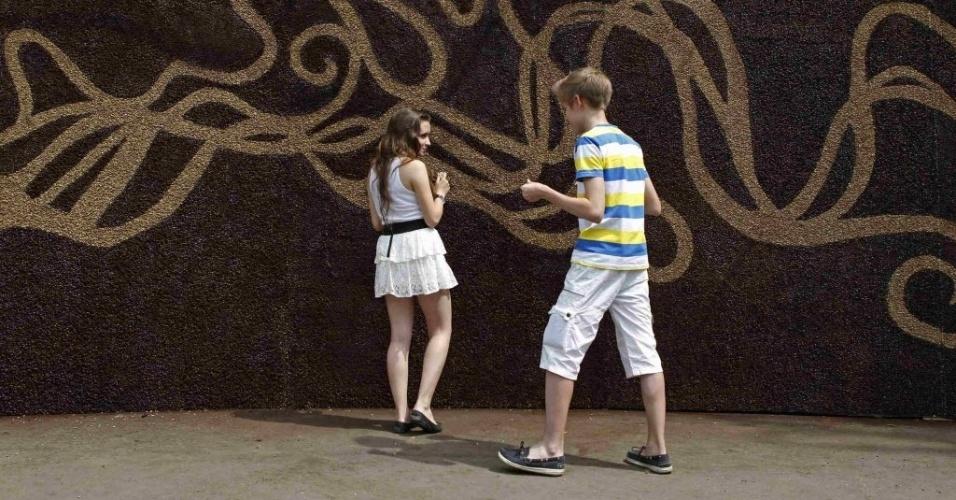 26.jun.2012 - Crianças põe grãos de café em quadro montado no parque Górki, em Moscou, capital da Rússia. Os organizadores do evento afirmam que o quadro, quando estiver pronto, ocupará uma área de cerca de 30 m², quebrando assim o recorde de maior obra da história feita de grãos de café