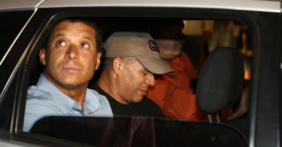 8.jul.2010 - O ex-policial Marcos Aparecido dos Santos (de bon&#233;), conhecido tamb&#233;m como &#34;Bola&#34; ou &#34;Paulista&#34;, chega ao Departamento de Investiga&#231;&#227;o da Pol&#237;cia Civil de Belo Horizonte. A pol&#237;cia acredita que ele tenha executado a morte de Eliza Samudio, ex-namorada do goleiro Bruno