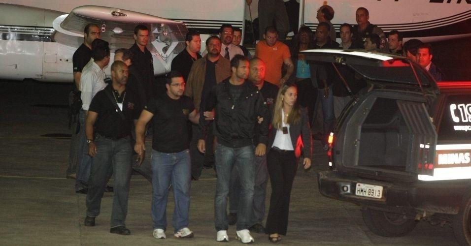 8.jul.2010 - O goleiro Bruno (ao centro) e o seu amigo Luiz Henrique Ferreira Romão, o Macarrão (de laranja, ao fundo), ao chegarem ao aeroporto de Pampulha, em Belo Horizonte (MG). A Justiça do Rio determinou a transferência atendendo a uma solicitação da Justiça mineira