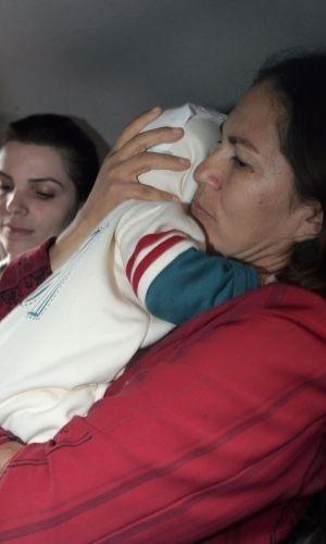 9.jul.2010 - Sônia Fátima Moura carrega o neto Bruno, filho de Eliza Samudio, cujo suposto pai é o goleiro Bruno Souza, acompanhada por conselheiros tutelares em Foz do Iguaçu (PR) nesta sexta-feira (9). A Justiça retirou o direito à guarda do avô, Luiz Carlos Samudio, e o concedeu à avó