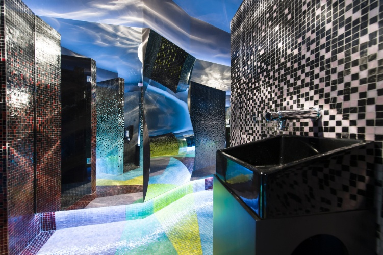 No Banheiro Unissex Caleidoscópio, a arquiteta Crisa Santos brinca com o jogo de espelhos. O sistema de áudio integrado é invisível - as caixas de som estão integradas às paredes recobertas por pastilhas de vidro, o que provoca uma sensação de que o som sai delas