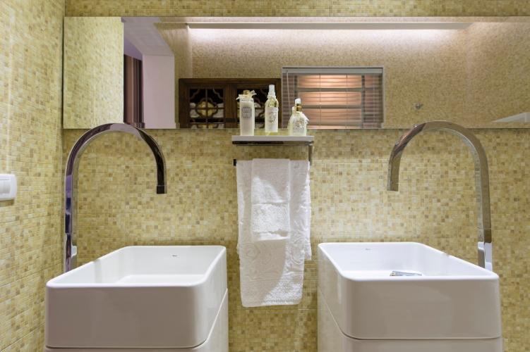 O banheiro na Casa da Montanha, assinada por Cynthia Pimentel Duarte, segue nos tons terrosos do restante da casa. O espaço é marcado pelas louças brancas, a parede revestida por pastilhas e um armário de madeira - com referência ao clima das montanhas