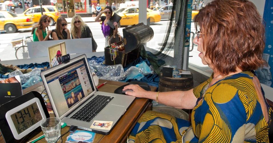 27.jun.2012 - Em uma loja de Oakland, em Nova Jersey (EUA), Kathleen Henkel, 68, tenta bater a marca de 30 horas seguidas em uma maratona de jogos virtuais de cartas no Facebook. Henkel disputa com outro jogador que está em Londres, na Inglaterra