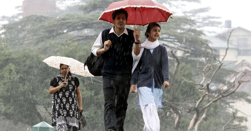 27.jun.2012 - Estudantes se protegem de chuva na cidade de Shimla, no norte da &#205;ndia