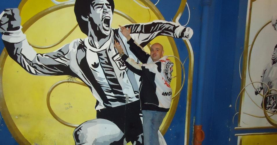 Corintianos posam para foto com o dedo em riste diante de imagem de Maradona nas cercanias de La Bombonera