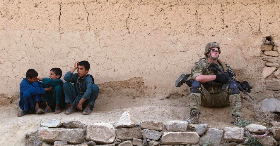 Crianças brincam ao lado de soldado que patrulha a cidade de Manugay, no Afeganistão