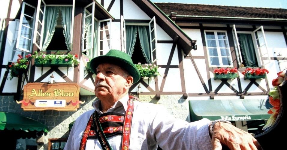 28.jun.2012 - Morador com traje típico alemão posa diante de casa na cidade de Blumenau; Santa Cataerina teve, na última década, crescimento populacional de 16,8%