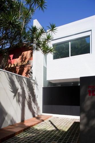A fachada frontal já anuncia a residência em linhas contemporâneas, com empena preta contrastando com todo o restante da casa, em branco. A garagem, totalmente aberta tem piso permeável e um deck lateral para a entrada. Destaque para o volume em balanço da suíte que se projeta 90 cm para a frente. O projeto é assinado pelos arquitetos e proprietários Lourenço Gimenes (escritório FGMF) e Clara Reynaldo (escritório CR2)