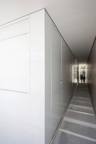 A passarela de malha expandida forma um corredor de acesso às duas suítes e finaliza na abertura frontal com fechamento em vidro. A empena da direita é revestida por ladrilho hidráulico e a parede da esquerda recebeu lambri de alumínio, além de embuir a rouparia e a sapateira do casal