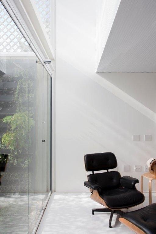 A sala de estar integrada ao jardim se torna uma área de descanso. A chaise longue desenhada por Charles Eames é colocada num ponto estratégico da sala: junto ao jardim e no vão com 5,14 m de pé-direito, o que significa abundância de luz natural. O projeto da residência é assinado pelos arquitetos e proprietários Lourenço Gimenes (escritório FGMF) e Clara Reynaldo (escritório CR2)